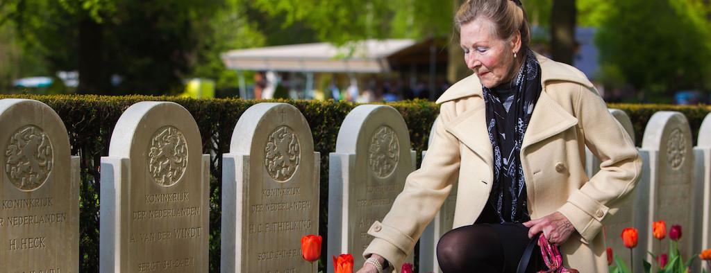 vrouw legt bloemen bij een graf
